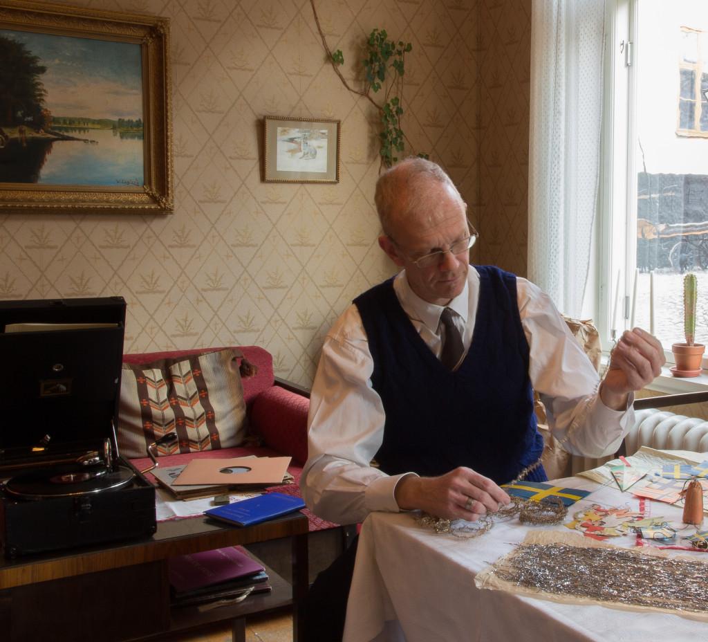 I huset arbetar far med att göra i ordning grandekorationerna. På vevgrammofonen av märket His Masters Voice från 1930 spelas julmusik på stenkakorna. Foto: Tomas Wiedersheim-Paul