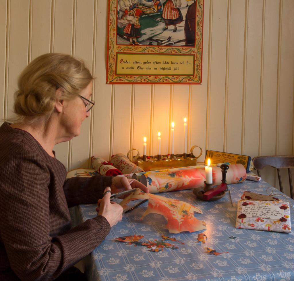 I köket klipper frun ut julmotiv från julklappspapper för att sedan fästa det på kaklet med lim av kokt potatismjöl. Foto: Tomas Wiedersheim-Paul