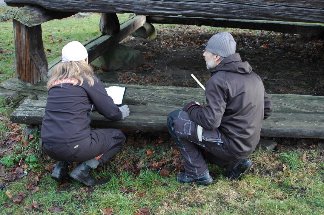 Marianne och Olof mäter syllramen under härbret från Tjärnmyra vid Delsbogården. Foto: Boel Melin