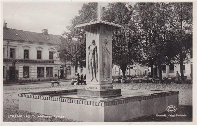 """Ett hjälpsamt bidrag från Facebook-gruppen """"Du vet att du är från Strängnäs om.."""": Ett vykort med fontänen """"Årstiderna"""" av O. Ahlberg med Ekstedt & Frankes järnhandel i bakgrunden. Med reservation för att upphovsrätten är okänd."""
