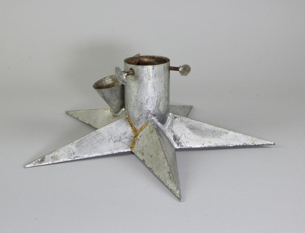 Julgransfot i plåt, i form av en femuddig stjärna. Cylinderformat fäste med tre skruvar. På en av stjärnans uddar en tratt för påfyllning av vatten. I Åhlén & Holms katalog från år 1917 säljs denna typ av julgransfot till ett pris av 4 kr och 95 öre. Det finns uppgifter om att man kunde köpa stjärnan så sent som 1927.