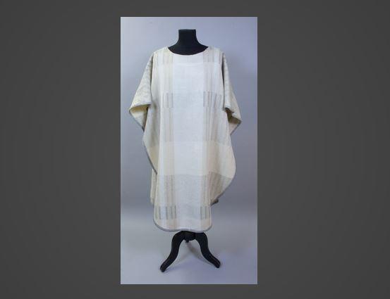 """Mässhake, formgiven av textilkonstnär Sofia Widén och utförd på Nordiska museets konserveringsateljé 1960. Handvävd i drällvariation, med ränder i satin eller mönstrade. Varp av vitt lingarn, inslag ullgarn i naturvitt samt tre grå toner i olika breda ränder. Kantad runtom med snedremsa av grått tuskaftsvävt linnetyg. Mitt bak och mitt fram brett lodrätt parti med vit satinväv. Enkel tungformad modell med något bredare axelparti och något insvängt i sidorna fram. På bakstyckets vita linrand en korsformad utsmyckning, där korsets fyrkantiga mitt utgörs av en applikation av grått linnetyg (eller band). Korsarmarna utförda med broderi, läggsöm med silver- och guldtrådar (kallade gnister och soutage på ritningen) i ett fyrkantigt mönster. Dessutom """"strålar"""" uppåt och neråt av samma metalltrådar. Ofodrad. Tungorna förstärkta eller lagade på insidan nertill med vanlig grå snedremsa."""